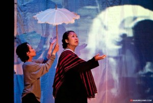 Two women on stage with an umbrella and light from Aimee's play A History of the Body
