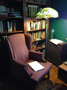 Chair with laptop, lamp, and bookshelves in writer Pamela Hart's studio