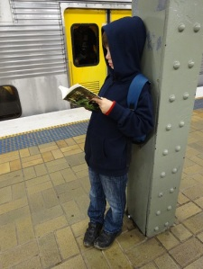 Mr. 8 reading The Mapmaker Chronicles: Prison of the Black Hawk by A. L. Tait in train station after SWF 2015