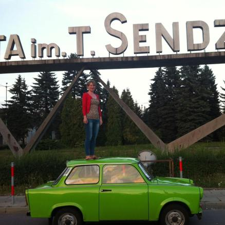 Magdalena McGuire standing on a green trabant