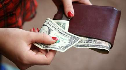 Woman's hand taking dollars out of a wallet