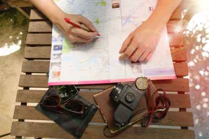 Woman consulting map with travel ephemera around her