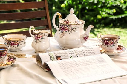 Tea set and magazine set up on table outside