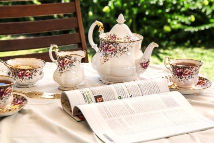 Tea set and magazine set up on table outside