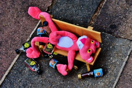 Drunk pink panther on bench surrounded by empties