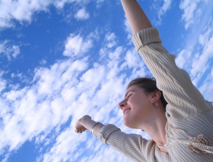 Rejoicing woman with arms reaching towards sky