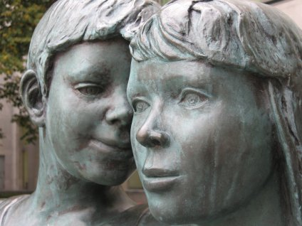 Sculpture of boy whispering to woman